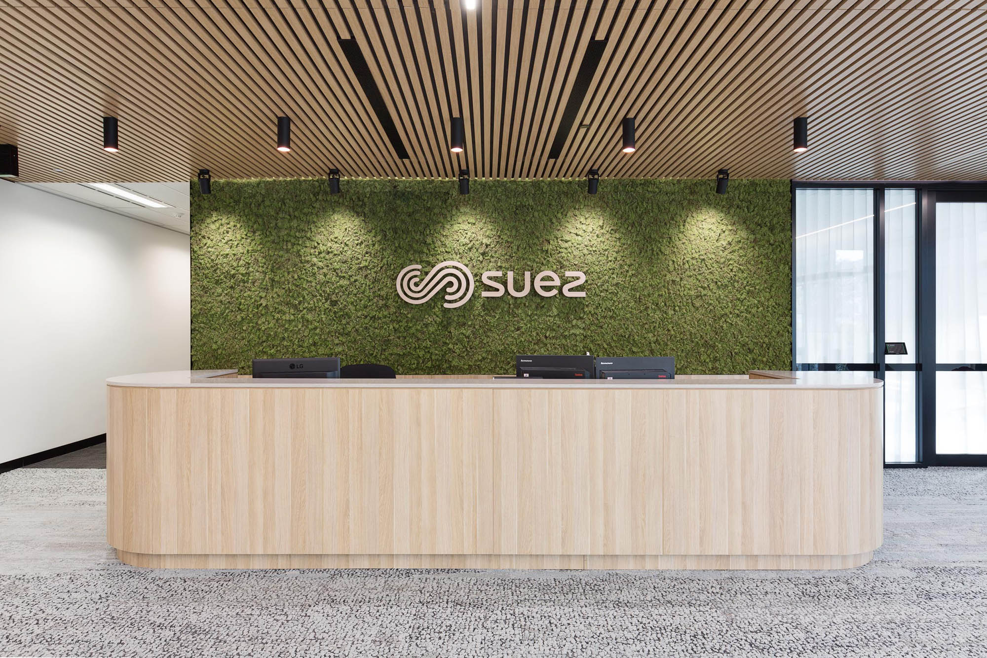 suez office fitout timber reception desk and green wall
