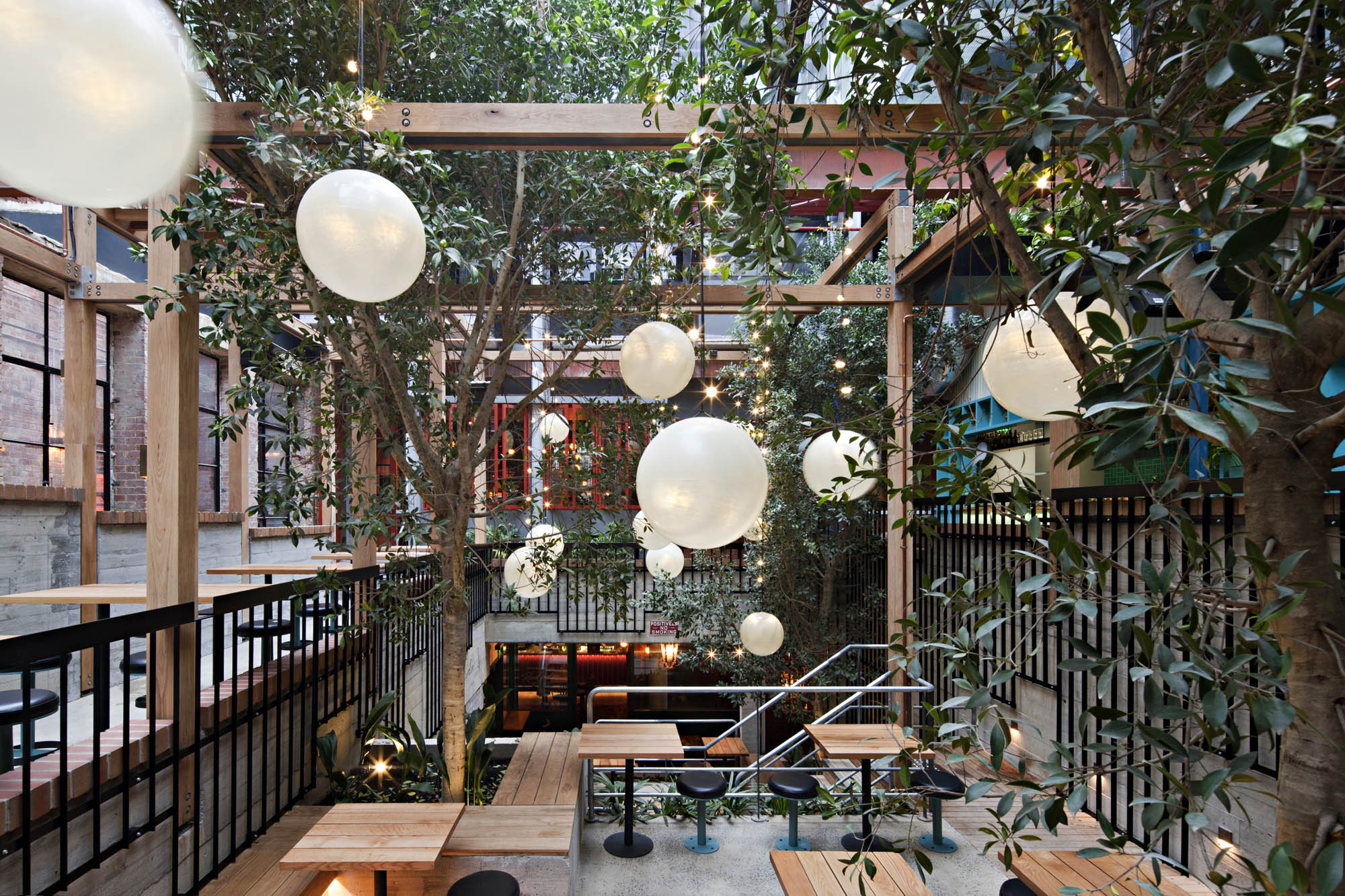 garden state hotel melbourne fitout alfresco dining outdoor pendant lighting trees stairs