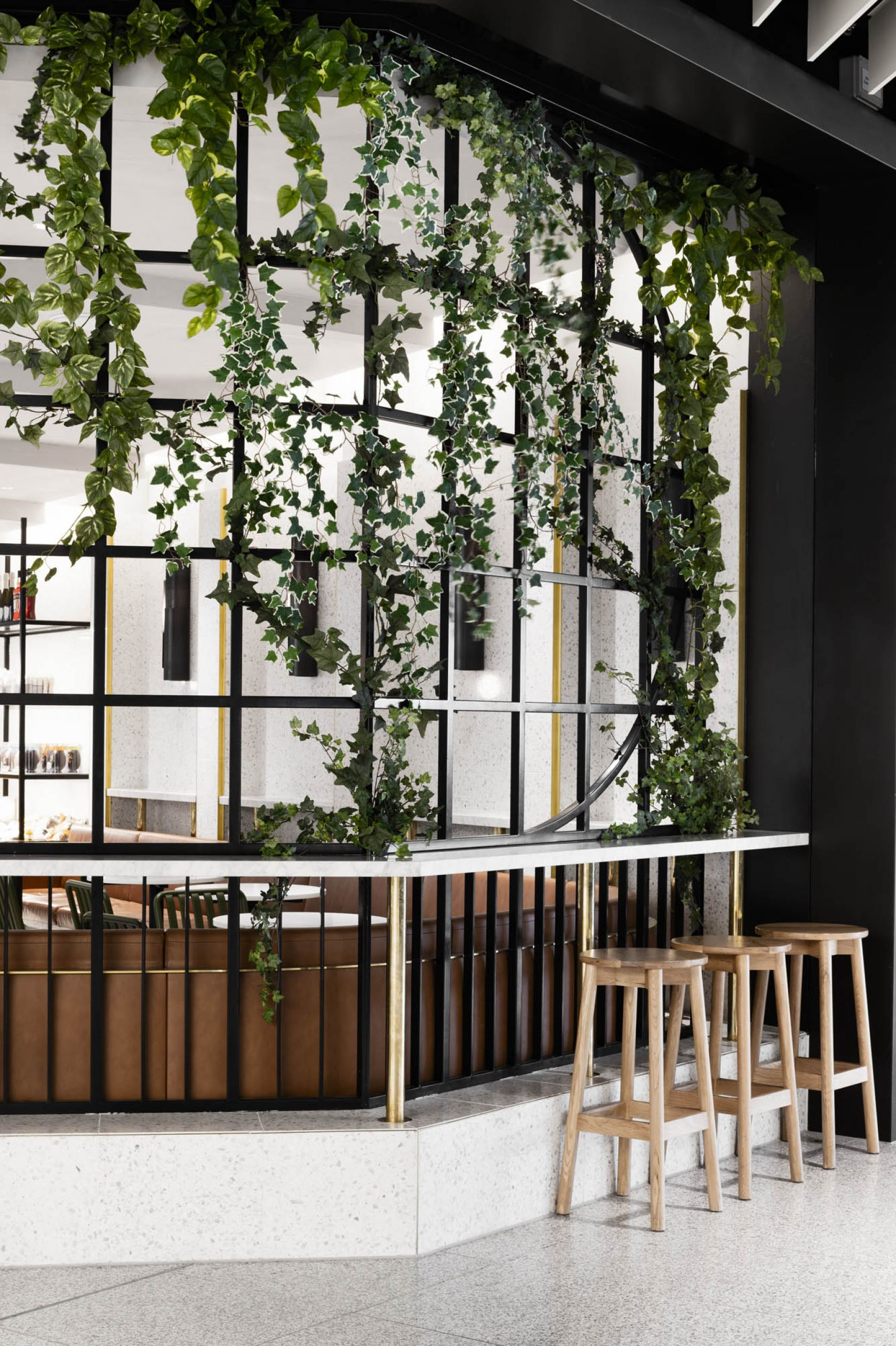 brunetti t2 hospitality interior fitout vic melbourne airport greenery stools table exterior