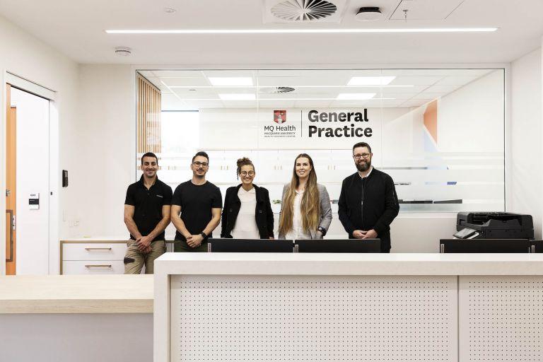 mq health general practive staff team standing in front of desk